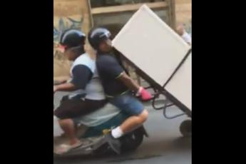 Napoli, frigorifero trasportato in scooter. Il video è virale sul web